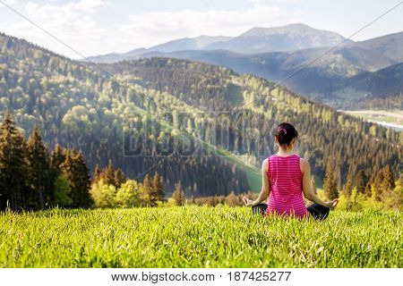 Young people sitting on a mountaintop. The concept of a healthy lifestyle travel and yoga.