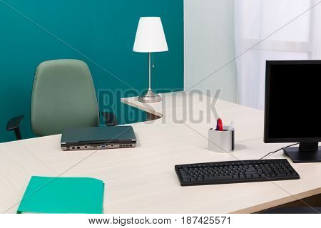 laptop and monitor on a desk in a modern office