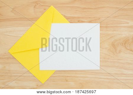 An embossed blank white card with yellow envelope on a desk with copy space for your message