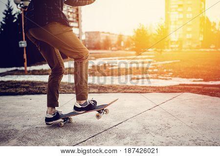 Man young skateboarder legs skateboarding at skatepark On Sunset. Concept tricks and jumping on a skateboard