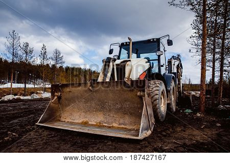 Machine tractor loader with bucket front in front of the sky. Concept road construction.