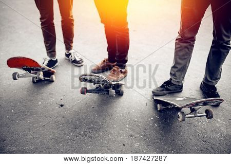 group of friends skateboarders keep a foot on the skateboard. The concept of doing street sports company.