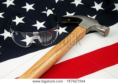 A wood handled hammer and safety glasses on an American flag