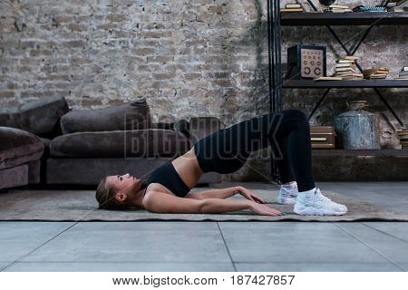 Sporty girl doing floor hip raise or butt lift exercise lying on floor in her loft apartment.