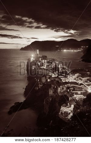 Vernazza at night with buildings on rocks over sea in Cinque Terre, Italy. Black and white.