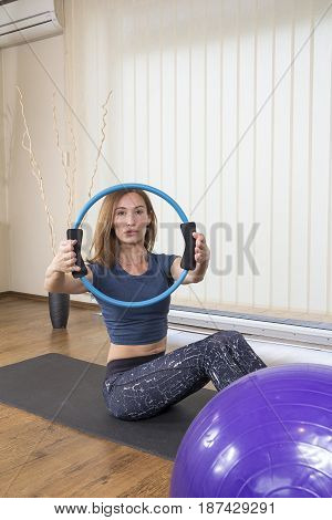 Attractive Fit Woman Exercise with Pilates Magic Circle