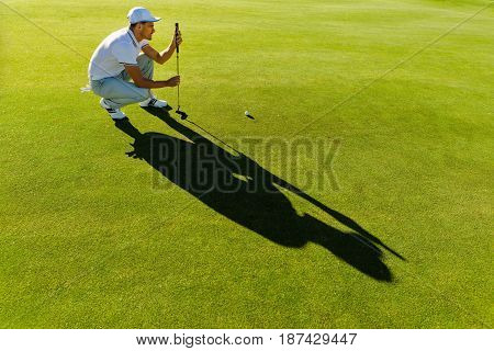 Male Golfer Check Line For Putting Golf Ball