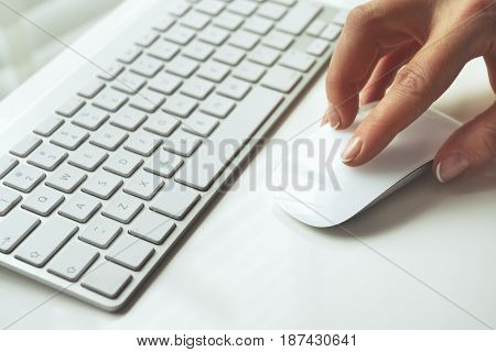 Closeup of hand using computer mouse. Closeup of businesswoman hand using computer mouse with laptop keyboard in the background