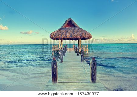 Tropical white sandy beach. Palm leaf roofed wooden pier with gazebo on the beach. Punta Cana Dominican Republic