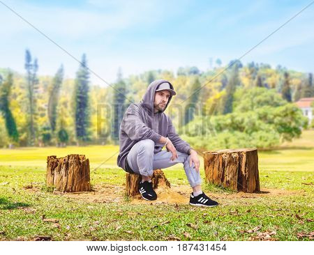 Rapper sitting on a stump, forest on background