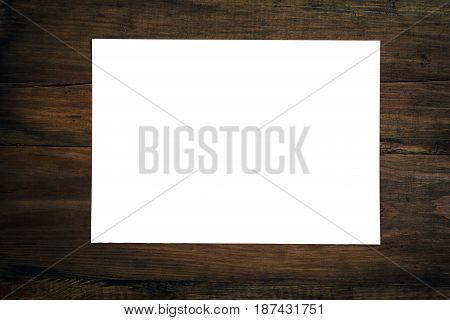 Blank sheet of white paper on dark wooden desk. Business concept. Template
