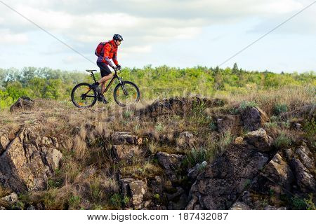 Cyclist in Red Jacket Riding the Mountain Bike on the Beautiful Rock. Extreme Sport Concept