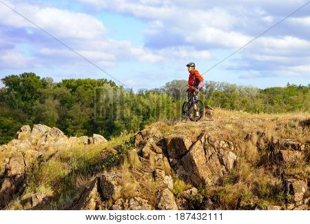 Cyclist in Red Jacket Resting with the Mountain Bike on the Beautiful Rock. Extreme Sport Concept