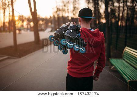 Roller skater with skates in hands, back view