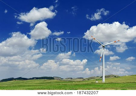 Wind generator turbine in a green field and blue sky with clouds - ecology energy saving concept