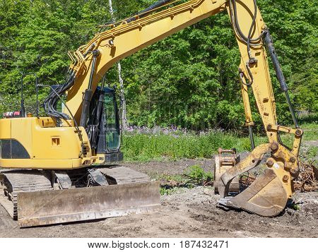 Excavator in the forest preparing construction of the hiking trail