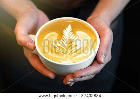 Cup of coffee. Latte art made by barista focus in milk and coffee. Vintage color