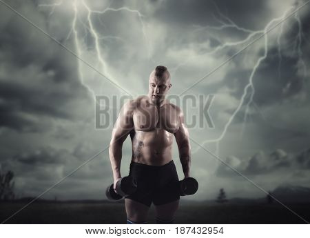 Athlete with dumbbells, lightning in dark sky