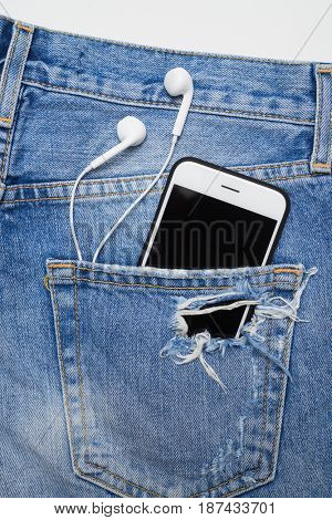 Top view of a cellphone with headphones in the pocket of ripped denim shorts. Summer vacation items