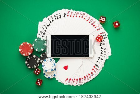 online casino concept, playing cards, dice chips and smartphone. online casino with copyspace on the green table. top view of online casino concept. banner template layout mockup for online casino and gambling.