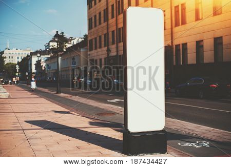 Vertical narrow information board in urban settings with road and crosswalk around empty curved mock-up banner blank billboard with copy space place for advertising message logo or your text