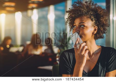 Young curly black female in luxury office space recording audio message via her smartphone afro american teenage curly girl using her cell telephone as recorder to send voice message to her mother
