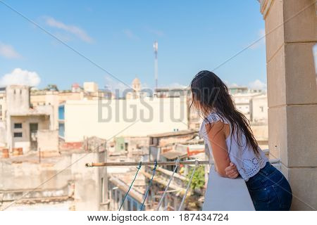 Young attractive woman in red dress on old balcony in apartments in Havana