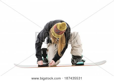Sport girl with a snowboard isolated on white. Snowboarder girl fastens bindings on snowboard