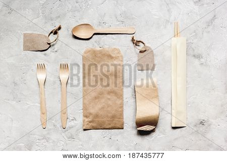 food delivery service workdesk with paper bags and flatware on restourant stone table background top view mockup