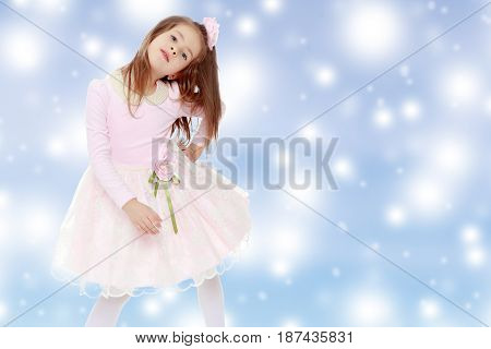 Dressy little girl long blonde hair, beautiful pink dress and a rose in her hair.She put forth a foot.Blue Christmas festive background with white snowflakes.