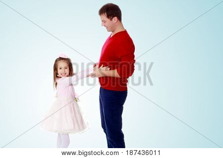 Cute little long-haired girl in a smart pink dress , reaches out to his dad.