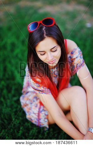 Beautiful portrait of adorable modest smiling girl with closed eyes painted with red ends of long hair sitting on the grass in the forest on blurred background close-up.