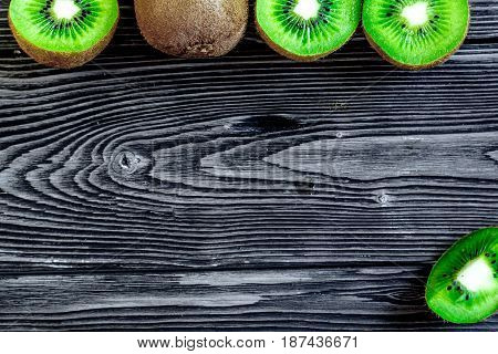 fresh green fruits with kiwi on dark wooden desk background top view mock-up