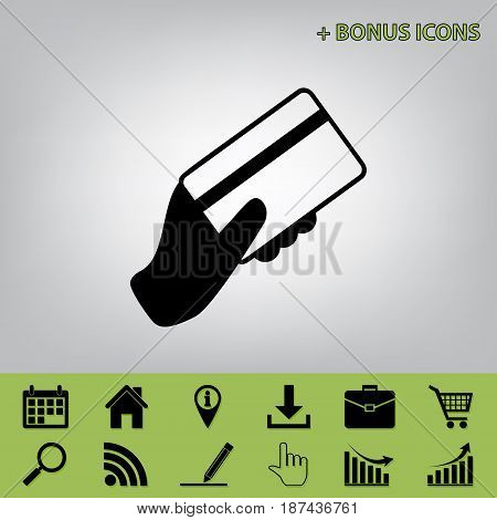 Hand holding a credit card. Vector. Black icon at gray background with bonus icons at celery ones