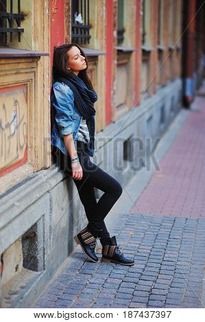 Portrait of a young long haired cute brunette woman in denim jacket and pantsthoughtfully standing near the wall of an old building side view