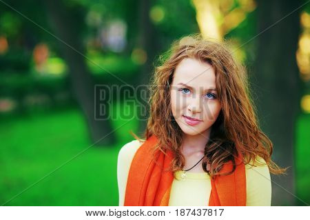 Portrait of a gorgeous girl with wavy brown hair beautiful blue eyes walking in summer Park close-up blurred background.