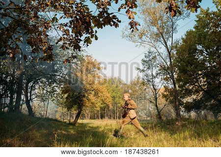 Dyatlovichi, Belarus - October 2, 2016: Re-enactor Dressed As Russian Soviet Red Army Soldiers Of World War II Running To Enemy Positions In Autumn Forest During Historical Reenactment.