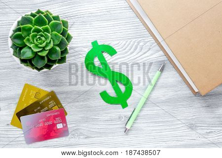 student's desk with dollar sign for fee-paying education set gray wooden background top view mock up
