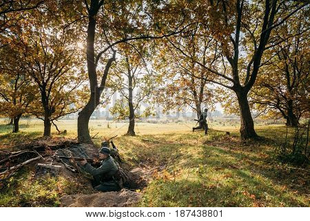 Dyatlovichi, Belarus - October 2, 2016: Re-enactors Dressed As German Wehrmacht Infantry Soldier In World War II Hidden Sitting With Rifle Weapon In An Ambush In Trench In Autumn Forest At Sunrise