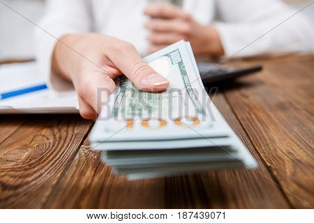Hands of person proposing money to you - closeup shot