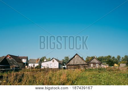 Old Russian Traditional Wooden Houses In Village Or Countryside Of Belarus Or Russia Countries. Sunny Blue Sky In Summer Day.