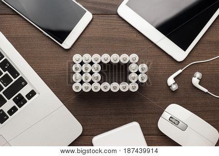 conceptual image of battery charge level pictogram made of rechargeable batteries with some mobile devices that use battery accumulators like smart phone, tablet computer, laptop and power bank. battery concept on brown wooden table