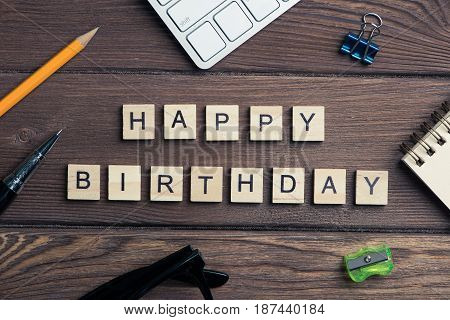 Happy Birthday spelled in game letters on wooden background
