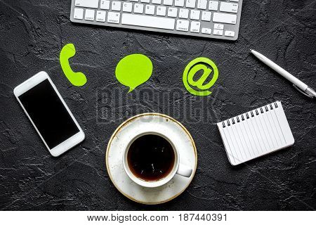 e-mail contact us concept with internet icons and mobile on dark work desk background top view mockup