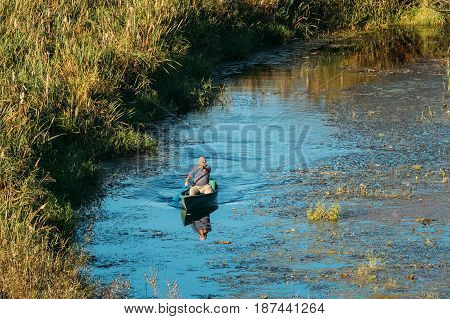 Gomel, Belarus - September 6, 2016: Man Fishing From Old Wooden Fishing Boat In Summer Lake Or River. Beautiful Summer Sunny Day Or Evening. Russian Nature. Ecotourism.