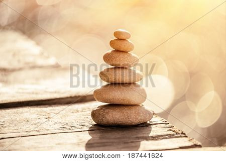 Spa stones still life on the beach, stack of pebbles on the boardwalk over sea in sunset light, peace and relaxation on summer vacation, balance in life concept