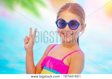 Portrait of a pretty baby girl wearing cute sunglasses on the beach, sweet kid smiling and shows the sign of peace by hand, happy summer vacation in the pool