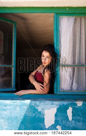 Relaxing young woman standing in the window of an old derelict house