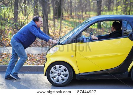MOSCOW - OCT 25, 2016: Man pushes Mercedes Smart with woman (models with releases) in Sokolniki where conducted Auto Show - Oldtimer, Gallery