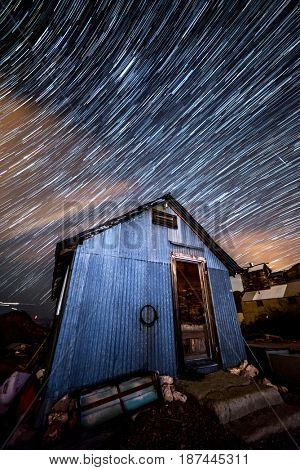 Star trail photography captures the path of distant stars framed against an old mining shack as the earth rotates.